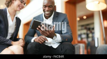 Heureux les jeunes gens d'affaires assis ensemble à l'aide de tablette numérique tout en hall de l'hôtel. L'accent sur l'ordinateur tablette.