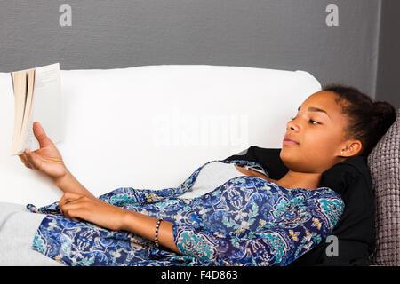 Jeune fille portant un canapé en lisant un livre. Banque D'Images