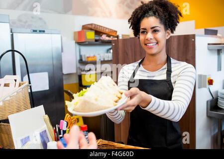 Serveuse servant le déjeuner au client Banque D'Images