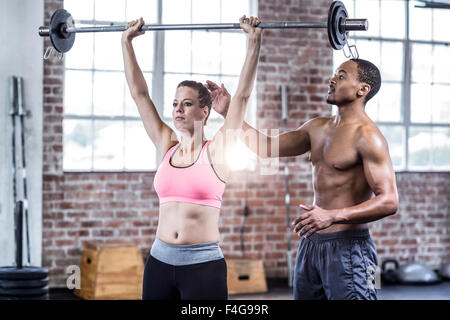 Trainer helping woman with barbell levage Banque D'Images