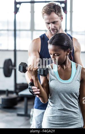 Male trainer assisting woman avec haltère Banque D'Images