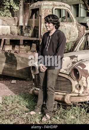 Boy leaning sur le capot d'une vieille voiture rouillée en ferraille. Banque D'Images