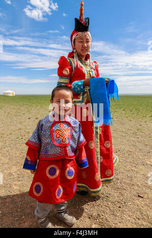 Femme et enfant en costume traditionnel (deel), bol en argent pour le lait d'accueil, près de ger, désert de Gobi, Banque D'Images
