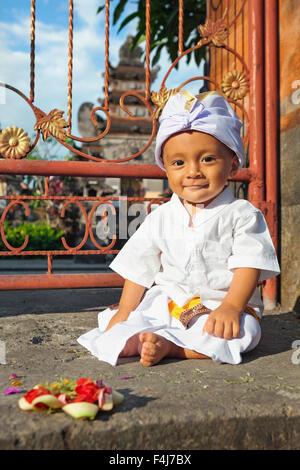Portrait de bébé garçon balinais avec visage souriant en costume traditionnel Sarong assis dans un temple hindou Banque D'Images