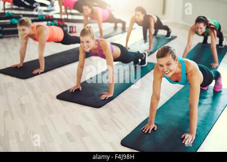 Grand groupe de jeunes femmes travaillant dans une salle de sport faire poussez se lève dans une classe d'aérobic Banque D'Images