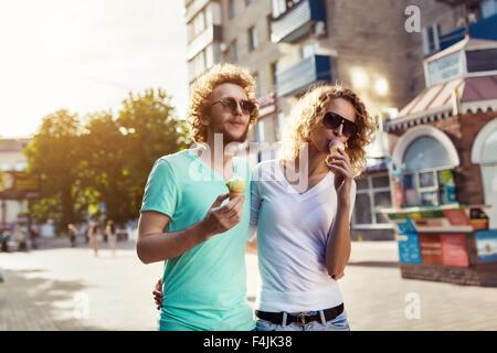 Beau jeune couple en train de marcher ensemble et de lécher la crème glacée Banque D'Images
