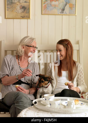 La Suède, Smaland, Retford, grand-mère avec sa petite-fille eatink les cookies et de rire Banque D'Images