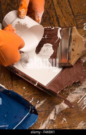 Bouteille de peinture et les pinceaux sur le plancher avec les taches de peinture multicolore Banque D'Images
