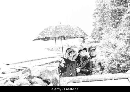 La neige en septembre et les touristes à l'abri sous un parapluie au lac Moraine, parc national Banff, montagnes Banque D'Images