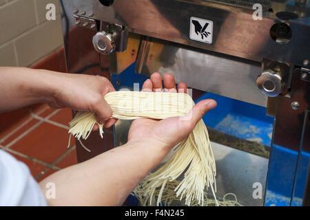 Chef cuisinier au restaurant japonais Muga faisant des nouilles Ramen avec une machine Banque D'Images