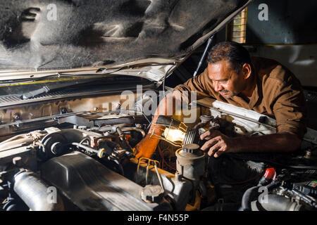 Un mécanicien répare une voiture bmw allemande dans un garage de la banlieue fort Banque D'Images