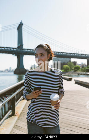USA, New York, portrait of smiling young woman with smartphone et café à emporter Banque D'Images