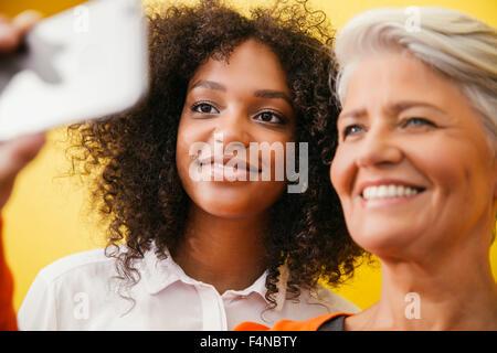 Deux femmes prenant un smartphone avec selfies en face d'un mur jaune Banque D'Images