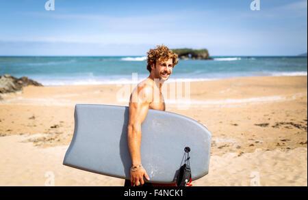 L'Espagne, les Asturies, Colunga, smiling surfer walking with bodyboard sur la plage Banque D'Images