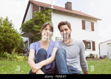 Portrait of smiling couple dans un jardin en face de maison résidentielle Banque D'Images