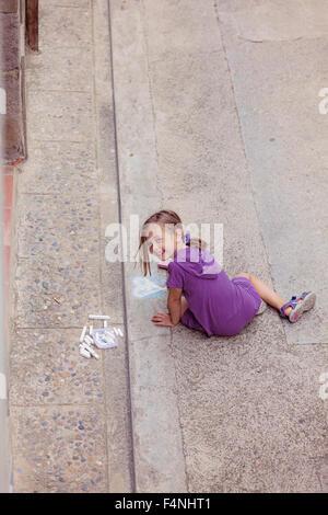 Smiling girl dessin avec crayon sur la rue Banque D'Images
