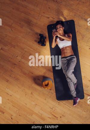 Vue aérienne d'aptitude femme couchée sur le tapis de sol en téléphone mobile. Vue supérieure de jeunes femmes de Banque D'Images