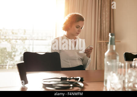 Image of businesswoman at conference table lecture du message texte sur son téléphone mobile. Caucasian female executive Banque D'Images
