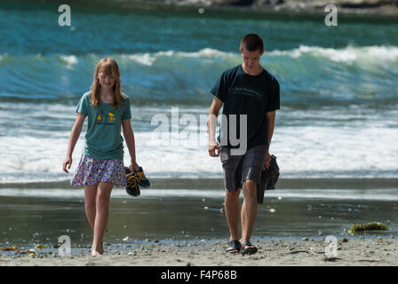 Un frère et une sœur de marcher le long de la plage de surf avec en arrière-plan, l'île de Vancouver, Colombie-Britannique, Banque D'Images
