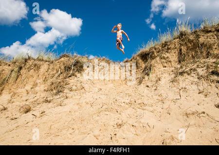La Suède, Halland, Halmstad, Tylosand, Boy (6-7) d'un saut d'un précipice de sable Banque D'Images