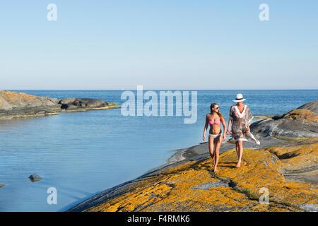 Mère et fille (16-17) marcher le long de plage de rochers Banque D'Images