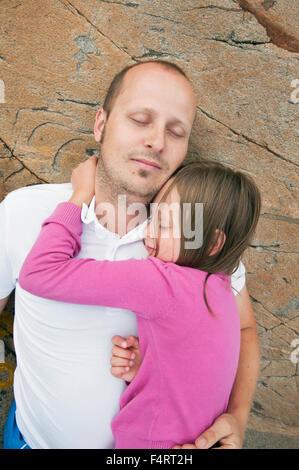 La Suède, Halland, Onsala, père et fille (6-7) lying on rock Banque D'Images