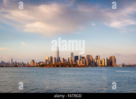 Gratte-ciel de New York et du quartier financier de Lower Manhattan à sunset light avec Battery Park et Ellis Island. Banque D'Images
