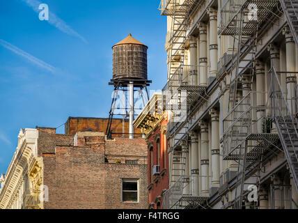 Réservoir d'eau en bois et façade en fonte d'immeubles en feu s'échappe, Soho, Manhattan, New York City Banque D'Images