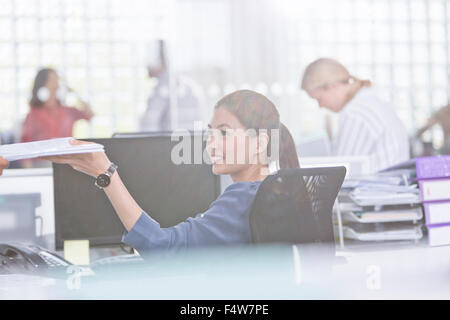 Smiling businesswoman holding paperwork at desk in office Banque D'Images