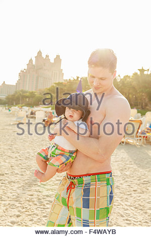 Homme tenant son (12-17 mois) on beach Banque D'Images