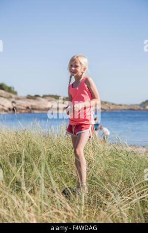 La Suède, la Côte Ouest Suédoise, Halland, Kungsbackafjorden, Girl (10-11) Comité permanent dans l'herbe par la mer