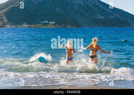 Grèce, Îles du Dodécanèse, Kalymnos, deux femmes en marche dans la mer Banque D'Images