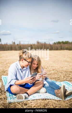 La Finlande, l'Aanekoski, Amerique, Girl (12-13) and boy (12-13) dans le champ de recherche et on mobile phone Banque D'Images