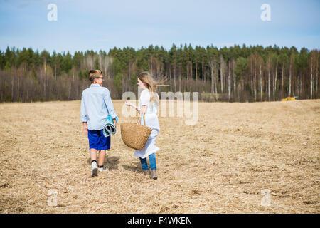 La Finlande, l'Aanekoski, Amerique, Girl (12-13) and boy (12-13) walking in field with forest on background Banque D'Images