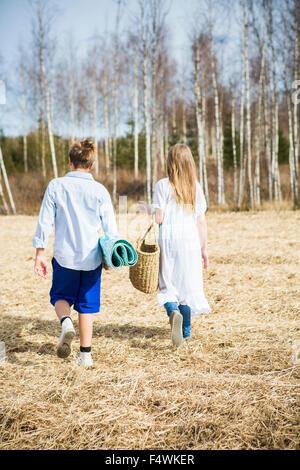 La Finlande, l'Aanekoski, Amerique, Rear view of girl (12-13) and boy (12-13) walking in field Banque D'Images