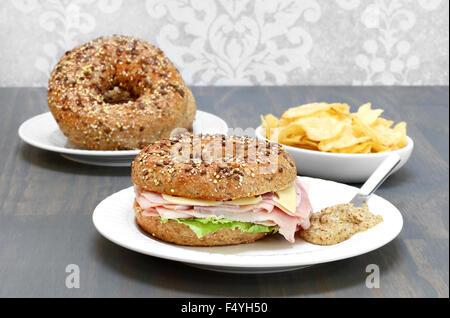 Jambon, fromage suisse et laitue sandwich sur un bagel de grains et de semences d'un côté de la moutarde piquante. Banque D'Images