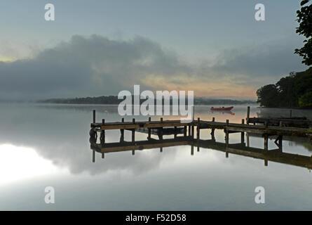Une jetée se dresse sur le lac Ullswater à Howtown au lever du soleil dans le Parc National du Lake District, Cumbria, Banque D'Images