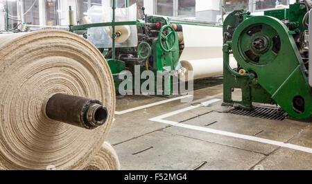 Usine de textile avec le rouleau en premier plan et les machines en arrière-plan Banque D'Images