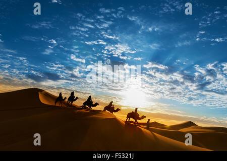 Caravane dans le désert pendant le lever du soleil contre un beau ciel nuageux, Erg Chebbi, Merzouga, Maroc. Banque D'Images