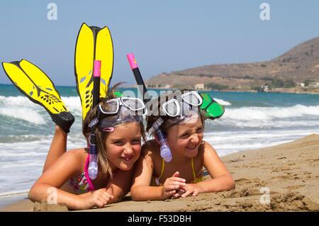 Jeunes filles posant sur une plage portant un équipement de plongée Banque D'Images