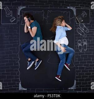 Jeune couple faire des activités au lit. L'homme est au téléphone alors qu'elle est en train de dormir. Banque D'Images
