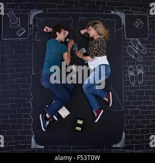 Jeune couple s'endormir tout en jouant à un jeu de société dans une chambre drawed avec de la craie sur papier. Banque D'Images