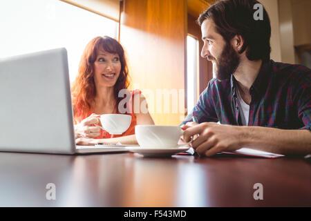 Les étudiants discutent dans la cafe en utilisant ordinateur portable Banque D'Images