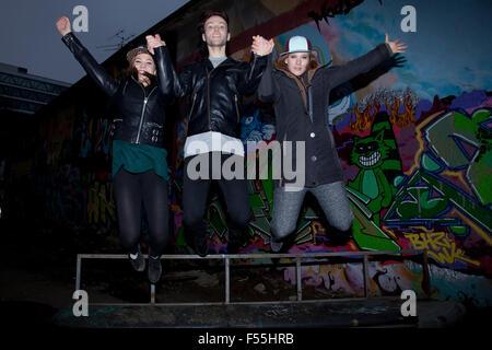 Groupe de danseurs de sauter devant un graffiti Banque D'Images