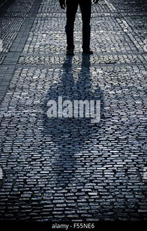 Homme Mystérieux figure debout dans une route pavée Banque D'Images