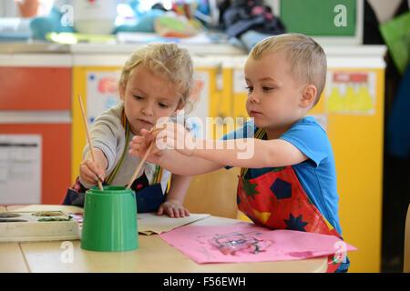 Une petite fille et garçon en peinture à l'école maternelle.