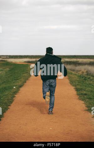 Homme d'âge moyen s'exécutant dans l'espace littoral rural Banque D'Images