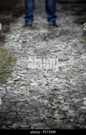 Les jambes de l'homme debout sur la terre craquelée Banque D'Images