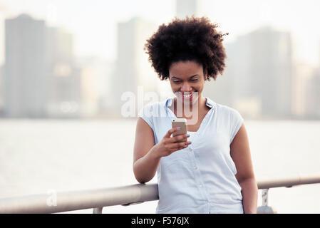 Une femme s'appuyant sur une rampe au bord de l'eau contrôler son téléphone portable Banque D'Images