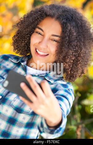 Beautiful happy mixed race African American girl smiling adolescent enfant de sexe féminin en tenant avec photographie Banque D'Images